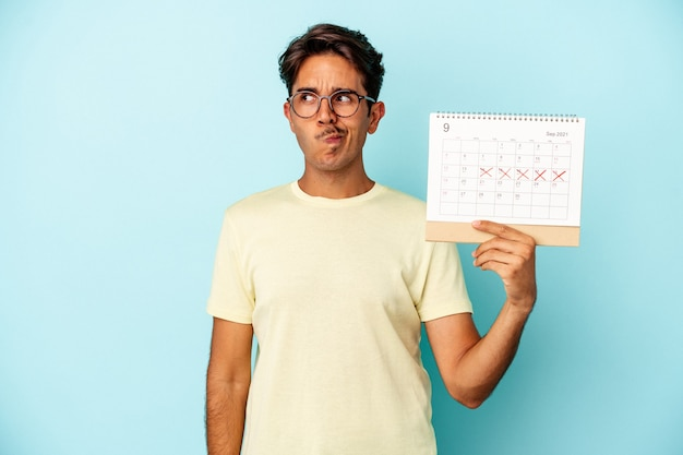 Młody człowiek rasy mieszanej posiadający kalendarz na białym tle na niebieskim tle zdezorientowany, czuje się wątpliwy i niepewny.
