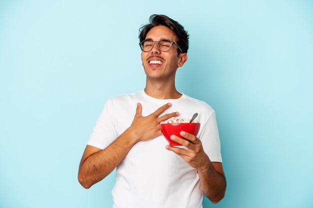 Młody człowiek rasy mieszanej posiadający zboża na białym tle na niebieskim tle śmieje się głośno trzymając rękę na klatce piersiowej.