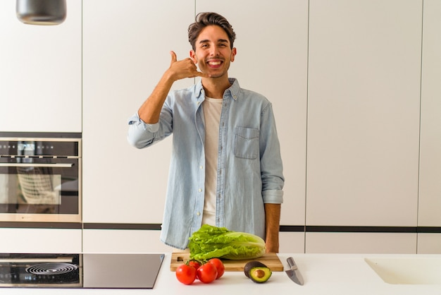Młody człowiek rasy mieszanej przygotowuje sałatkę na lunch pokazując gest połączenia z telefonem komórkowym palcami.