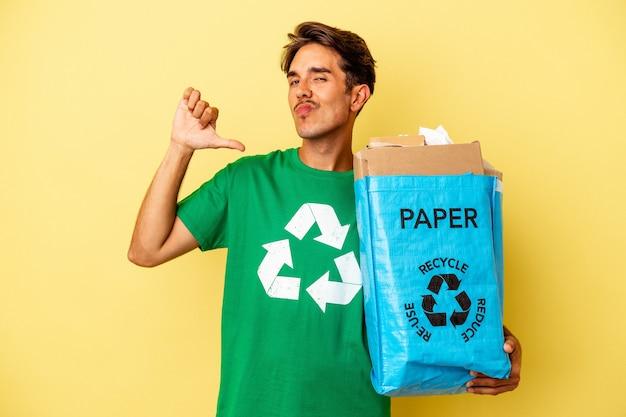 Młody człowiek rasy mieszanej recykling papieru na żółtym tle czuje się dumny i pewny siebie, przykład do naśladowania.