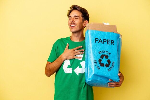 Młody człowiek rasy mieszanej recyklingu papieru na białym tle na żółtym tle śmieje się głośno trzymając rękę na klatce piersiowej.