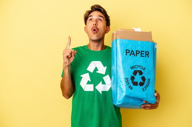 Młody człowiek rasy mieszanej recyklingu papieru na białym tle na żółtym tle, wskazując do góry z otwartymi ustami.