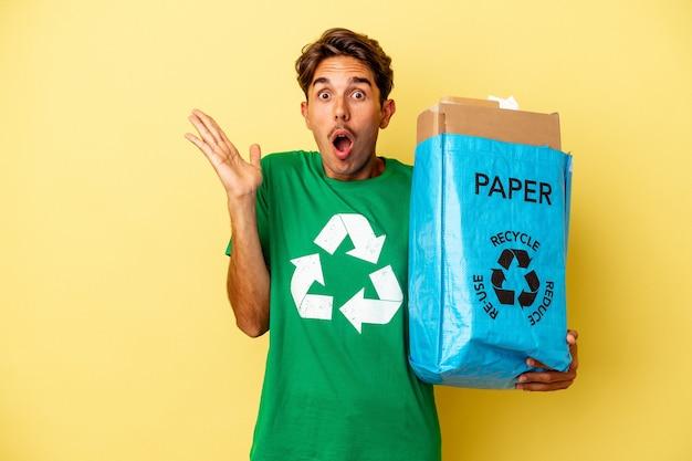 Młody człowiek rasy mieszanej recyklingu papieru na białym tle na żółtym tle zaskoczony i zszokowany.