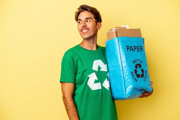 Młody człowiek rasy mieszanej recyklingu papieru na żółtym tle wygląda na bok uśmiechnięty, wesoły i przyjemny.