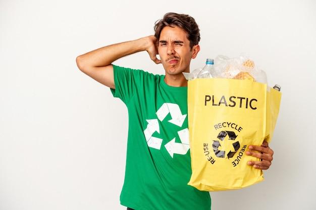 Młody człowiek rasy mieszanej recyklingu tworzyw sztucznych na białym tle na żółtym tle dotykając tyłu głowy, myśląc i dokonując wyboru.