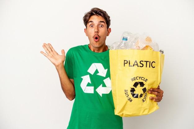 Młody człowiek rasy mieszanej recyklingu tworzyw sztucznych na białym tle na żółtym tle zaskoczony i zszokowany.