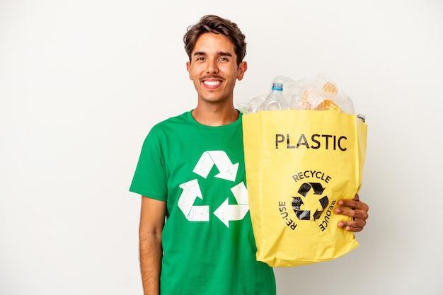 Młody człowiek rasy mieszanej recyklingu tworzyw sztucznych na żółtym tle szczęśliwy, uśmiechnięty i wesoły.