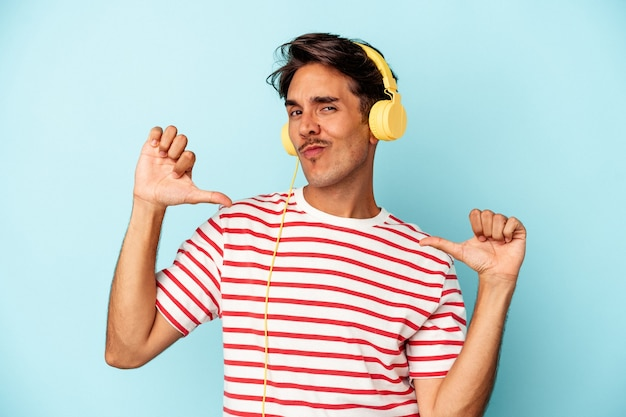 Młody człowiek rasy mieszanej słuchający muzyki odizolowanej na niebieskim tle czuje się dumny i pewny siebie, przykład do naśladowania.