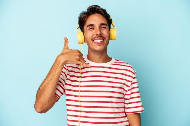 Młody człowiek rasy mieszanej słuchania muzyki na białym tle na niebieskim tle pokazując gest połączenia z telefonu komórkowego palcami.
