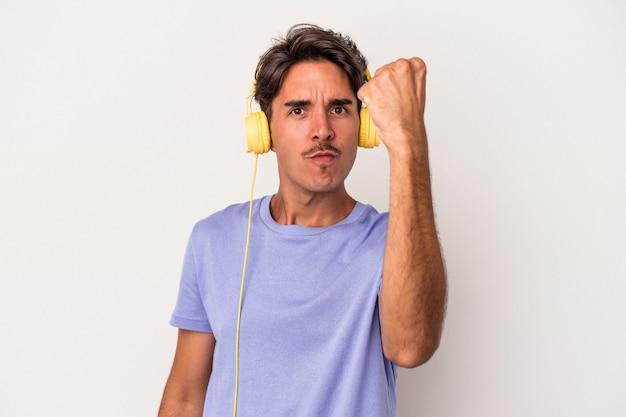 Młody człowiek rasy mieszanej słuchania muzyki na białym tle na niebieskim tle pokazując pięść do kamery, agresywny wyraz twarzy.