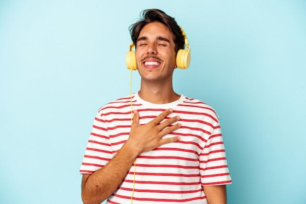 Młody człowiek rasy mieszanej słuchania muzyki na białym tle na niebieskim tle śmieje się głośno trzymając rękę na klatce piersiowej.