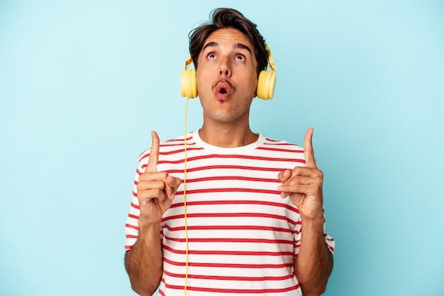 Młody człowiek rasy mieszanej słuchania muzyki na białym tle na niebieskim tle, wskazując do góry z otwartymi ustami.