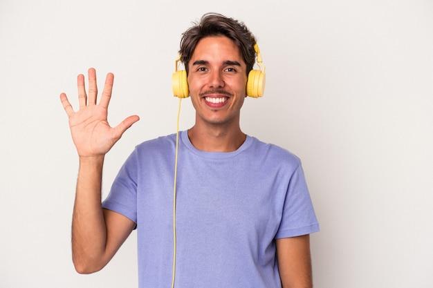 Młody człowiek rasy mieszanej słuchanie muzyki na białym tle na niebieskim tle uśmiechający się wesoły pokazując numer pięć palcami.