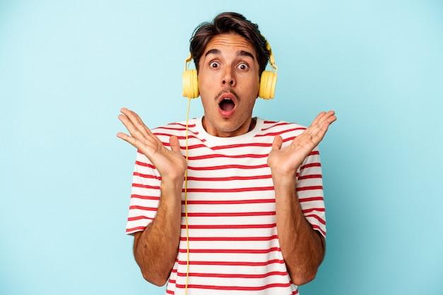 Młody człowiek rasy mieszanej słuchanie muzyki na białym tle na niebieskim tle zaskoczony i zszokowany.