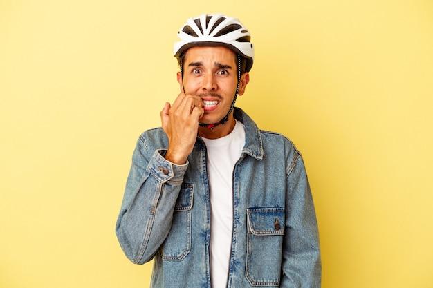 Młody człowiek rasy mieszanej sobie kask rowerowy na białym tle na żółtym tle gryzie paznokcie, nerwowy i bardzo niespokojny.