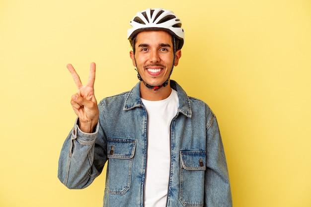 Młody człowiek rasy mieszanej sobie kask rowerowy na białym tle na żółtym tle pokazując numer dwa palcami.