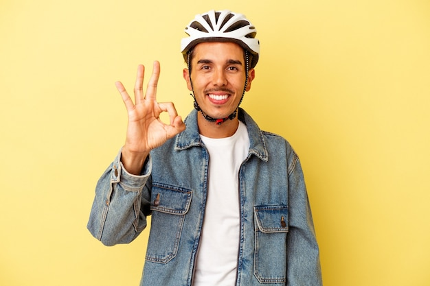Młody człowiek rasy mieszanej sobie kask rowerowy na białym tle na żółtym tle wesoły i pewny siebie, pokazując ok gest.