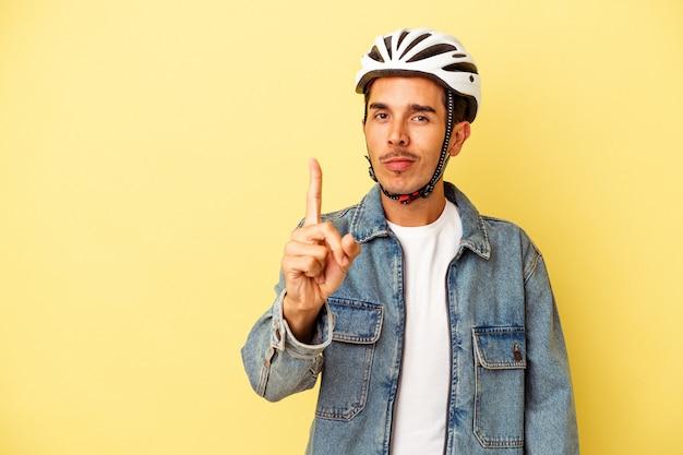 Młody człowiek rasy mieszanej sobie rower kask na białym tle na żółtym tle pokazano numer jeden palcem.