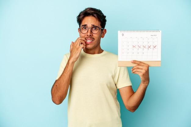 Młody człowiek rasy mieszanej trzymając kalendarz na białym tle na niebieskim tle gryzie paznokcie, nerwowy i bardzo niespokojny.