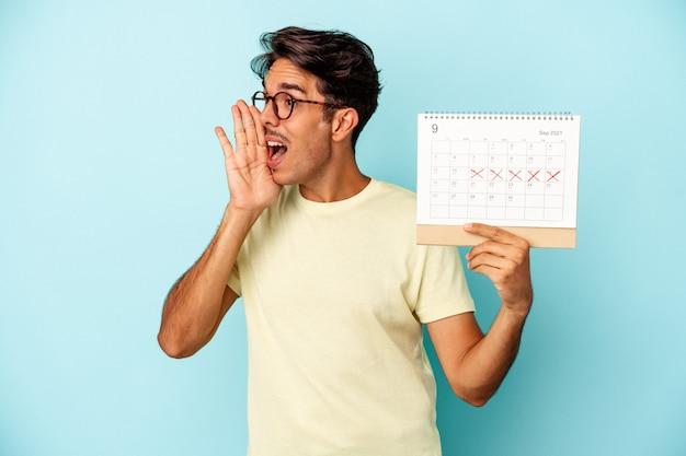 Młody człowiek rasy mieszanej trzymając kalendarz na białym tle na niebieskim tle krzycząc i trzymając dłoń w pobliżu otwartych ust.