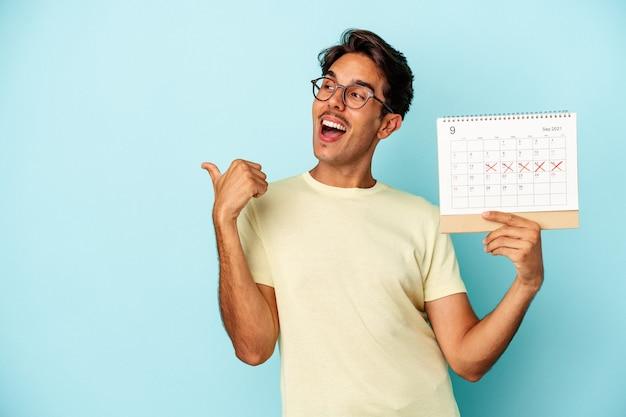 Młody człowiek rasy mieszanej trzymając kalendarz na białym tle na niebieskim tle punktów z palcem od kciuka, śmiejąc się i beztroski.