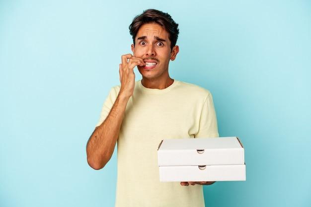 Młody człowiek rasy mieszanej trzymający pizze na białym tle na niebieskim tle gryzie paznokcie, nerwowy i bardzo niespokojny.