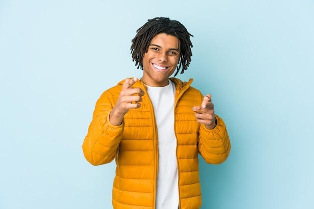Młody człowiek rasy mieszanej wesoły uśmiechy, wskazując na przód.