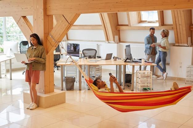 Młody człowiek relaksujący się w hamaku i korzystający z telefonu komórkowego z kolegami za pomocą cyfrowych tabletów, którzy spędzają czas w nowoczesnym biurze
