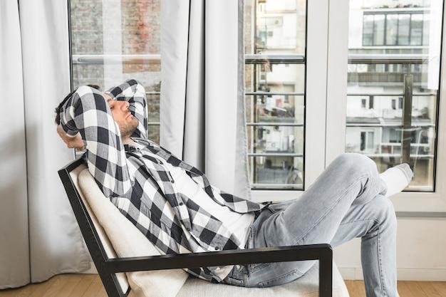 Młody człowiek relaksuje na krześle w domu