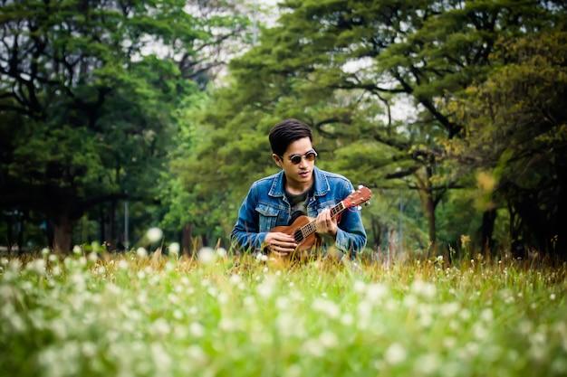 Młody człowiek relaksuje w parku z jego ukulele