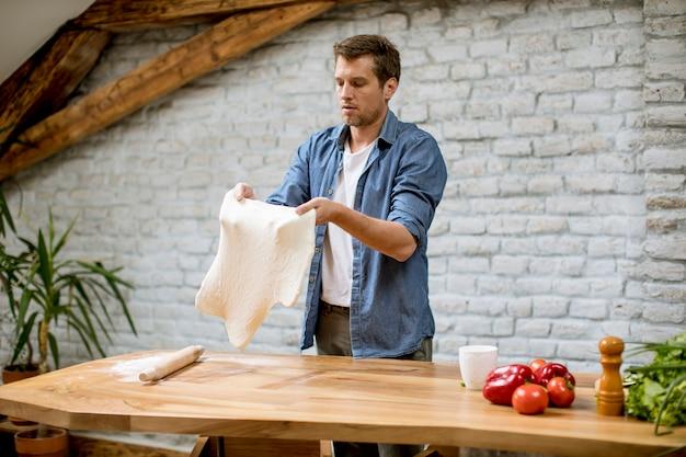 Młody człowiek robi ciastu w nieociosanej kuchni