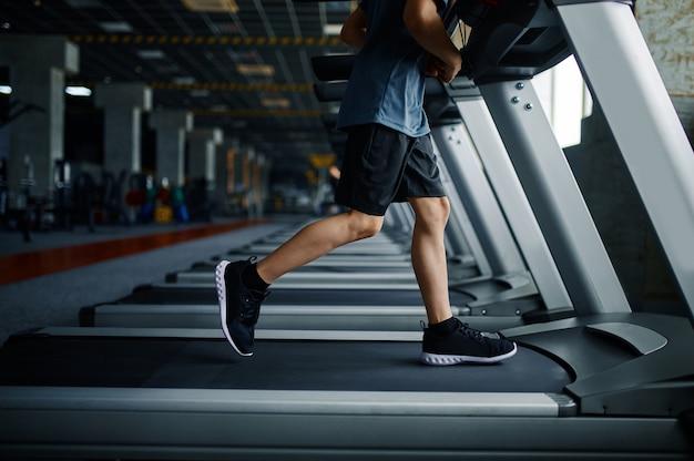 Młody człowiek robi ćwiczenia na bieżni w siłowni, uruchomiona maszyna. chłopiec na treningu w klubie sportowym, ochronie zdrowia i zdrowym stylu życia, dziecko na treningu