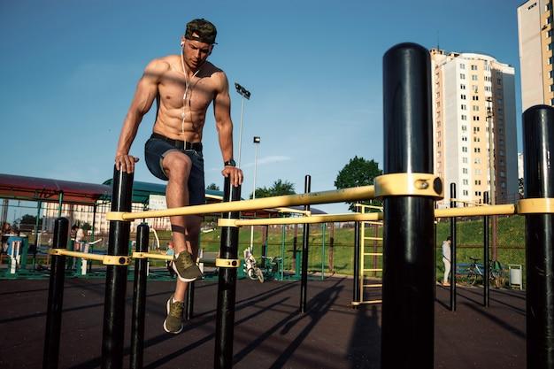 Młody człowiek robi ćwiczenia na nierównych barach na stadionie, sportowiec