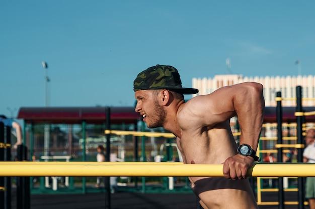 Młody człowiek robi ćwiczenia nierówne bary na stadionie, sportowiec, trening na świeżym powietrzu w mieście