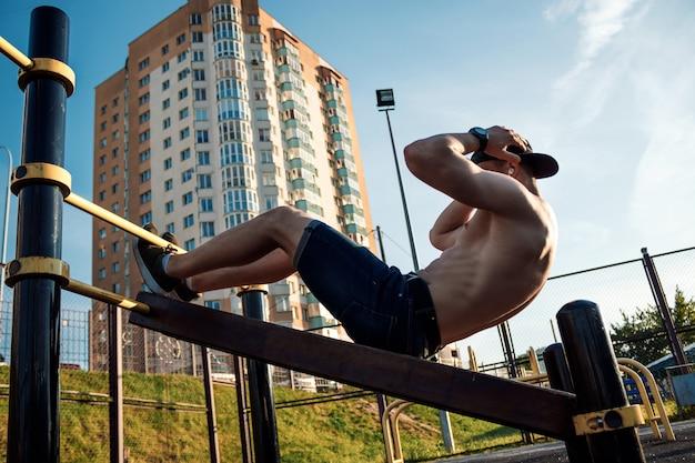 Młody człowiek robi ćwiczenia prasy na boisku sportowym, sportowiec, trening na świeżym powietrzu w mieście