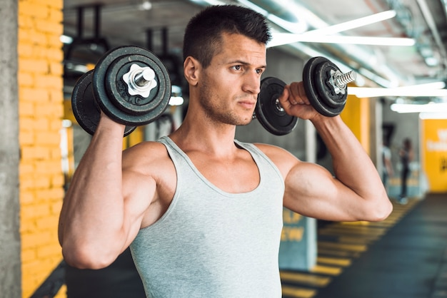 Młody człowiek robi ćwiczenia z hantlami na wzmocnienie jego ramię