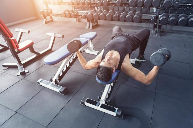 Młody człowiek robi ćwiczeniu dla abs mięśni w gym.