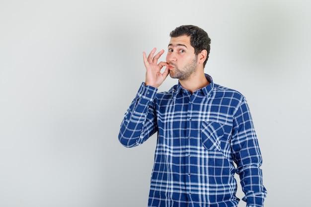 Młody człowiek robi gest blokady na ustach w kraciastej koszuli i wygląda poważnie