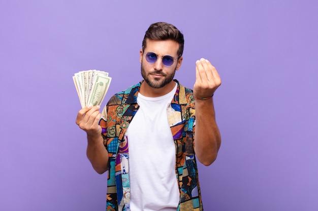 Młody człowiek robi gest capice lub pieniądze