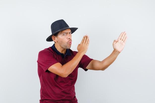 Młody człowiek robi gest kung fu w koszulce, kapeluszu i wyglądający pewnie. przedni widok.