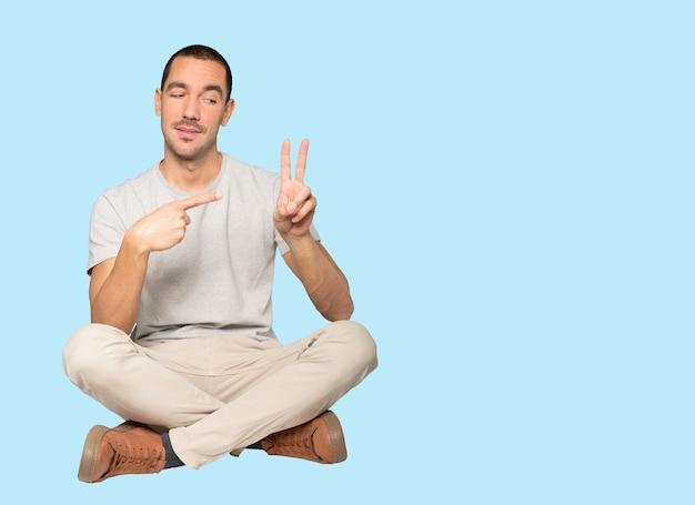 Młody człowiek robi gest numer dwa