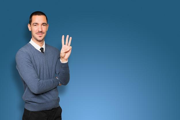 Młody człowiek robi gest numer trzy