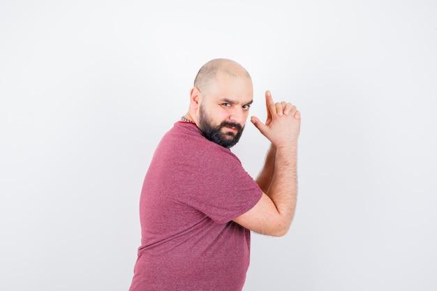 Młody człowiek robi gest pistoletowy w różowej koszulce i wyglądający odważnie.