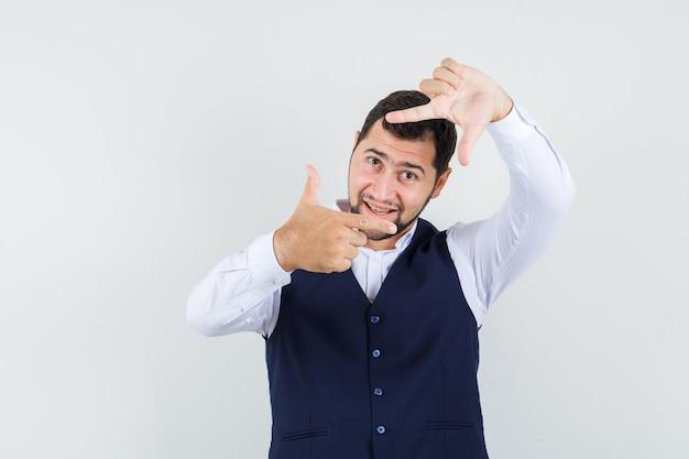 Młody człowiek robi gest ramy w koszuli, kamizelce i wygląda optymistycznie
