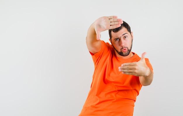 Młody człowiek robi gest ramy w pomarańczowej koszulce i wygląda pewnie. przedni widok.