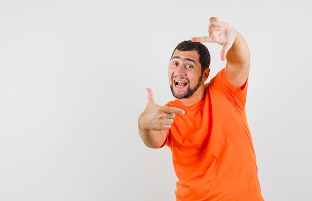 Młody człowiek robi gest ramy w pomarańczowej koszulce i wygląda wesoło. przedni widok.