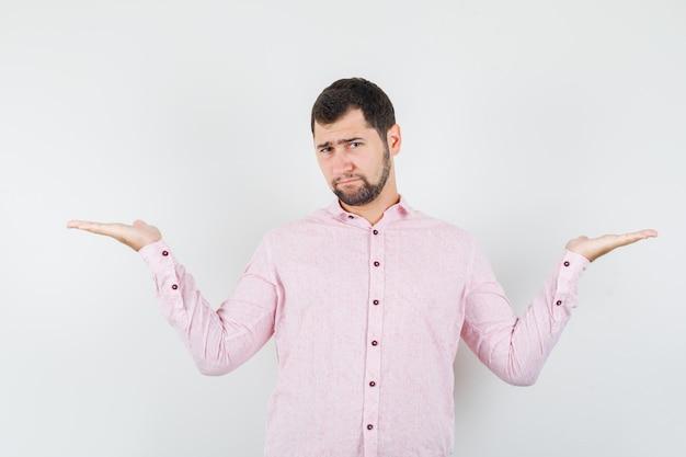 Młody człowiek robi gest wagi w różowej koszuli i wygląda ponuro