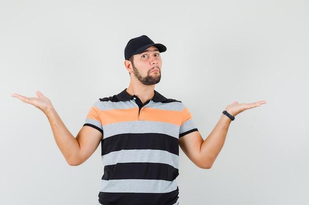 Młody człowiek robi gest wagi w t-shirt, czapka i patrząc zdezorientowany. przedni widok.