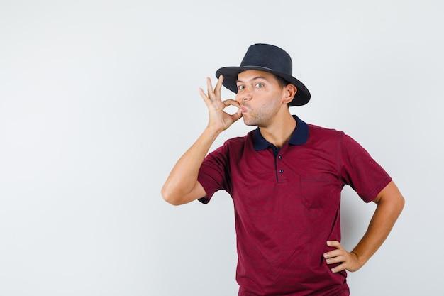 Młody człowiek robi gest zip w t-shirt, kapelusz i wygląda poważnie. przedni widok.