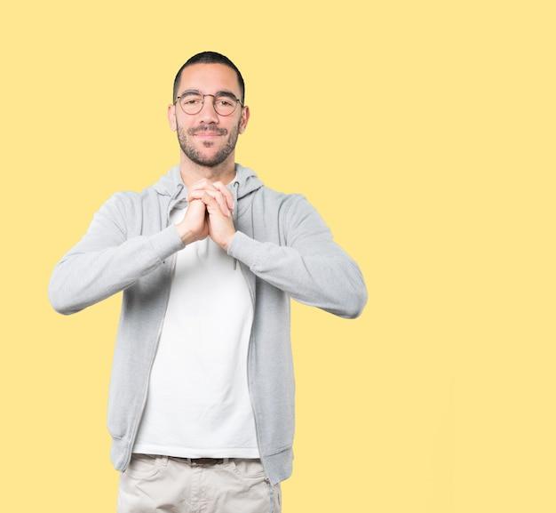 Młody człowiek robi gestowi drużynowej pracy z jego rękami
